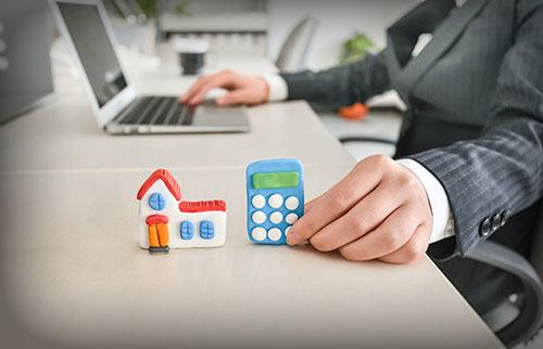 新築一戸建ての購入のためにパソコンで不動産物件を調べ、新築費用を電卓で計算するお客さま