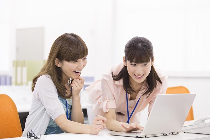 PCで新築業者を調べる女性二人