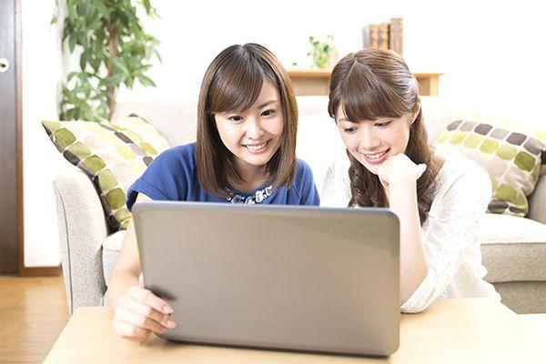 パソコンで不動産広告を見る女性二人