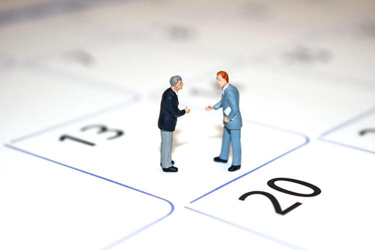 カレンダーの上でビジネスマン二人の会話