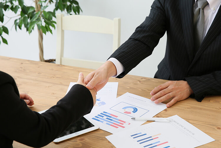 握手する住宅業者と新築購入者