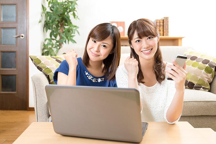 パソコンの前でガッツボーズをする女性2人