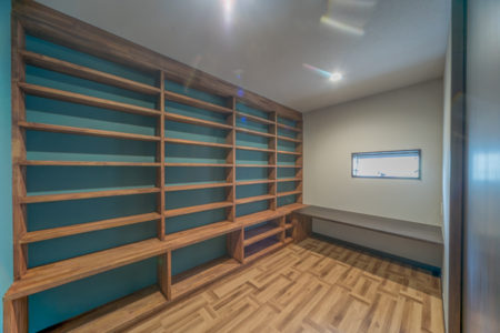 寝室には書斎が隣接しています。壁面いっぱいの本棚は、棟梁お手製の作品。カウンターの前に腰掛け、大好きな読書が楽しめる趣味室です。