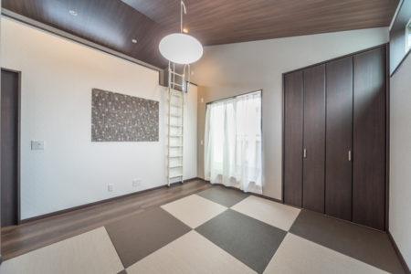 寝室は半帖畳敷きの和室。板間にTVや家電を置かれます。ロフトへ続く勾配天井には、ウッド調のクロスをコーディネート。