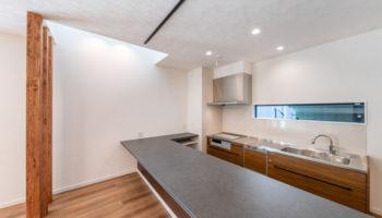 ヘアライン加工の壁付けキッチンと吊戸棚を利用した収納付き作業台